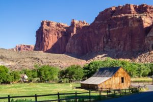 the red rock canyons with historic Gifford house in the foreground